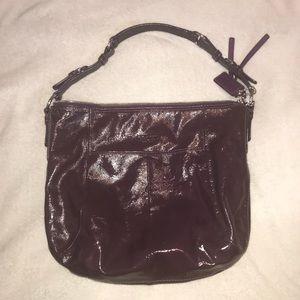 Dark purple patent leather Coach bag.
